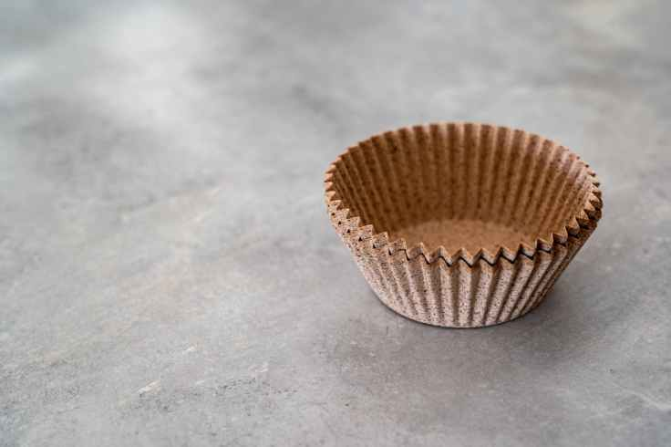 empty brown paper cup on gray surface